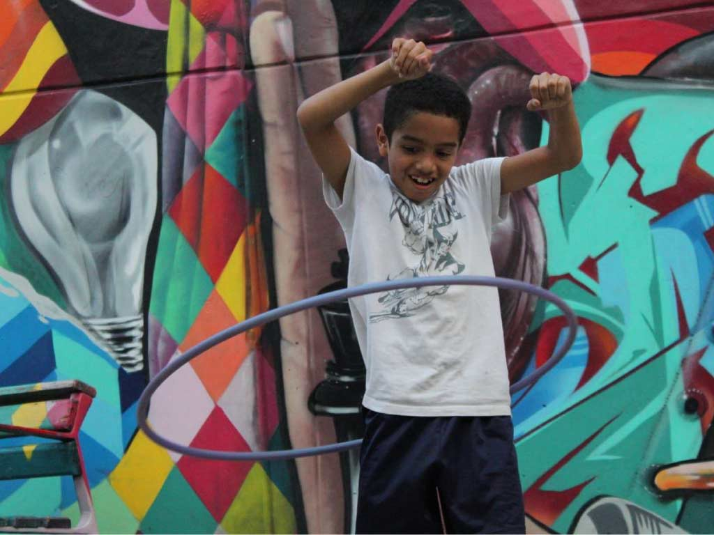 boy from san javier practando hula hula with graffiti background
