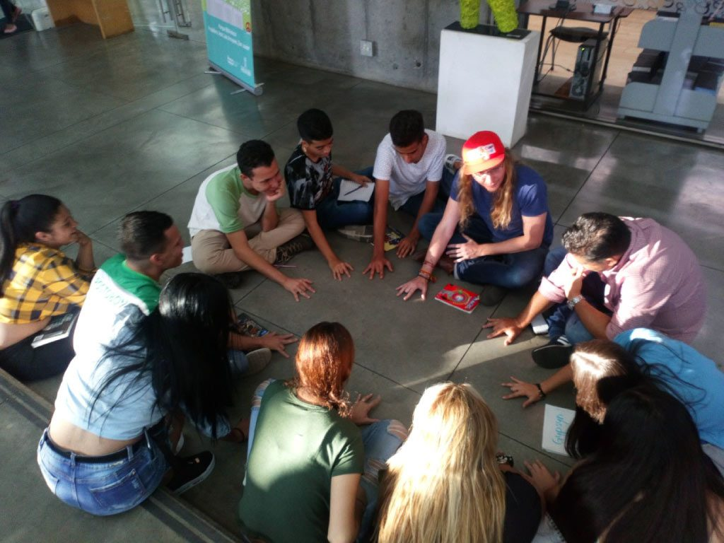 volunteer with students in a circle in front of the san javier library
